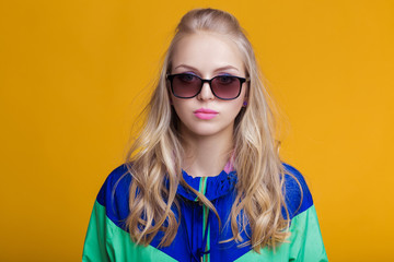 portrait of beautiful blond woman in sunglasses and blue green hooded jacket on yellow background. hipster summer.