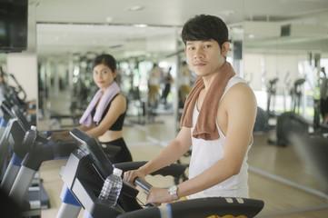 Keuken foto achterwand Fitness Young handsome man running on treadmill in gym
