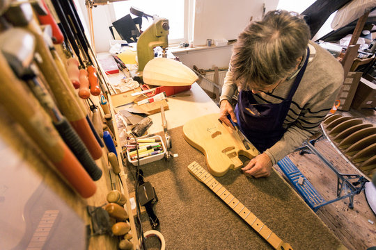Guitar repairer clearing the sawdust from an electric guitar