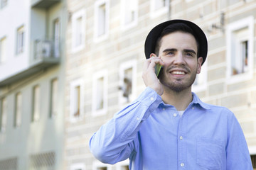 young man hipster attractive and modern talking on cellphone outdoors