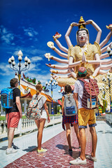 group of tourists looking at buddhist temple in thailand