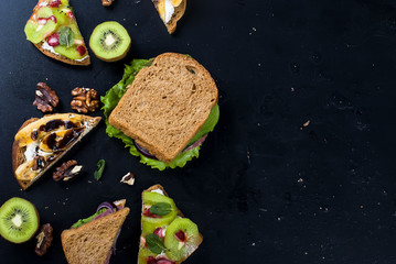 Tasty sweet sandwiches with bananas, nuts and chocolate, kiwi, strawberries and mint on black background