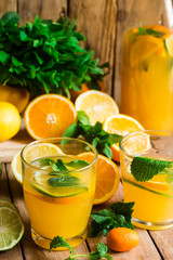 Refreshing citrus lemonade with fresh mint, glasses, bottle, cut fruits on wood kitchen table by window