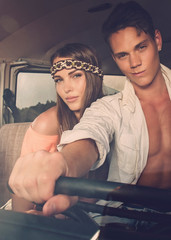 Hippie couple on a road trip driving van