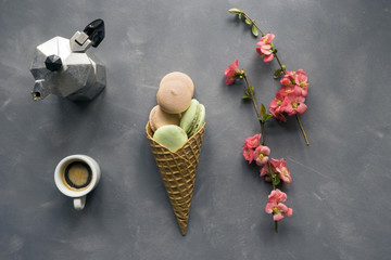 Coffee and macarons in ice cream cone on cement background