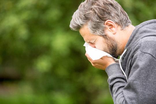 Mann mit Allergie beim Niesen