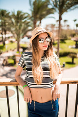 Portrait of relaxed happy smile young woman in hat and sunglasses on terrace of hotel on palms background. Summer vocation