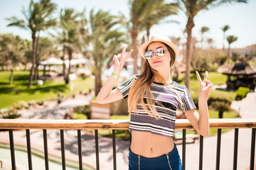Woman in hat and sunglasses with victory sign on summer resort. Summer vocation.