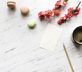 Top view of notebook, coffee, macarons and flowers on marble background