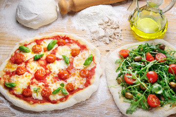 Homemade pizzas: Margherita with tomato and mozzarella. Vegetarian with arugula  cherry tomatoes and olives