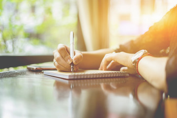 female hands with pen writing on notebook on wooden table ,young girl writing into her diary, in...