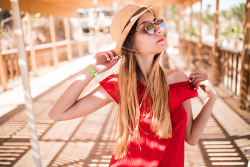 Young white girl standing on the pier in a red sun dress and hat. Summer vocation