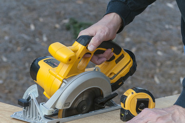 Working With A Power Circular Saw Cutting Wood With Tape Measure
