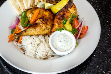 Pita bread, rice, grilled chicken and veggies on the plate