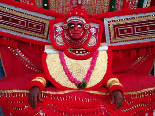 Artist of ancient art theater Kathakali in suit and mask: bright red wide clothing, garland of red flowers, red mask with metal eye sockets, Kerala, South India.