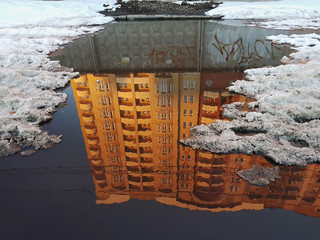 A puddle, in the surface of the water a reflection of a residential high house, lit by the orange rays of the setting sun, along the edges of the snow, winter in Kiev, Ukraine.