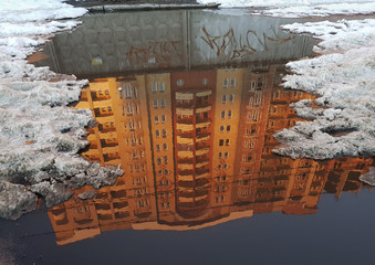Inverted diagonal reflection of an orange building in gray puddle, along the edges of broken pieces of white snow.