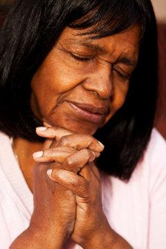 African American senior woman sitting on a bench praying.
