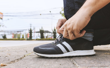 A man tie his sneaker shoes with soft-focus in the background. over light and film colors tone