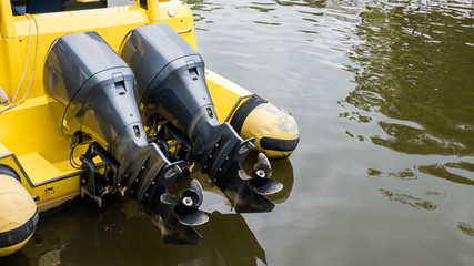 Close up of two motor boat engine propellers over yellow boat in water. Boat propellers concept with copy space.