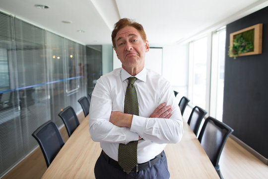 Skeptical senior businessman standing in boardroom