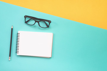 Flat lay design of work desk with notebook and glasses on green and yellow background.