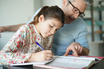 Man helping daughter with homework