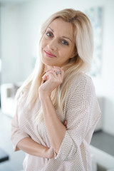 Portrait of beautiful blond woman standing at home