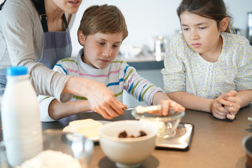 Mommy with kids baking cake together in home kitchen
