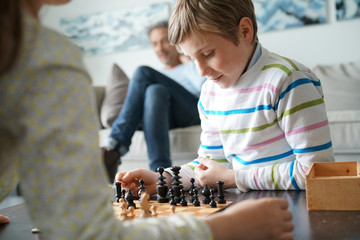 Kids playing chess game at home