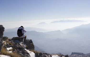 Hiker on the summit of a mountain and snow