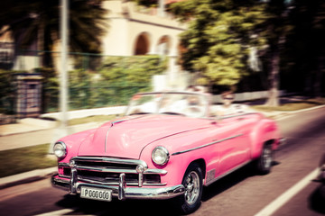 Tourists riding in oldtimer car in Havana. Concept of Cuba attractions.
