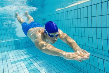 Schwimmer gleitet nach Startsprung unter Wasser