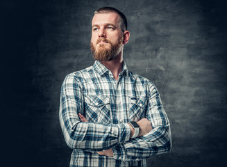 Bearded male dressed in a fleece shirt over grey background.