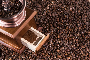 Elevated view of coffee mill with ground coffee on coffee beans