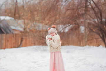 Cute smiling kid girl holding bunny walking in snow in park. Looking at camera. Childhood. Wearing knitted hat, sweater and skirt outdoors.