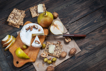 Camembert cheese with walnuts, honey and pears on rustic table