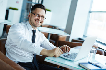 Bearded middle-aged businessman in eyeglasses distracted from work in order to pose for photography, laptop, glass of water and stationery located on cafe table