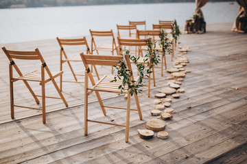 Compositions from the green hang on the chairs in the wedding ceremony area on the river bank