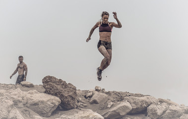 Strong beautiful muscular female athlete covered in mud jumping of a rough rocky ledge capture in mid air.  Wall mural