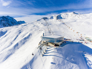 Ski resort in the Alps with ski lift and people skiing on the slope. Aerial view