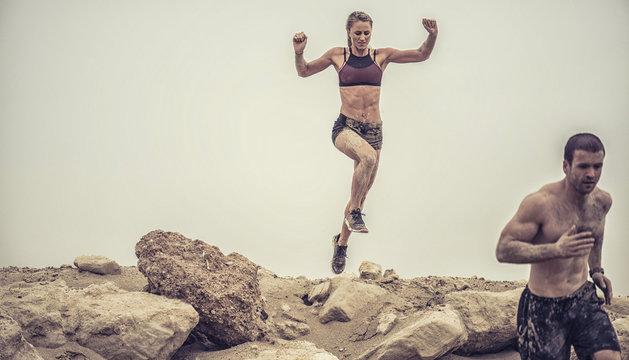 Strong beautiful muscular female athlete covered in mud jumping of a rough rocky ledge capture in mid air.