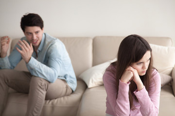 Unhappy couple quarrelling, sitting apart indoors. Aggressive guy is blaming woman, shouting at her. Annoyed girl ignoring man, not talking to boyfriend. Family problems concept, teenagers conflict