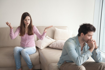 Couple arguing. Young woman speaking emotionally, blaming man, gesturing, explaining opinion. Unhappy girlfriend shouting to frustrated boyfriend, guy sitting back not talking to her. Family quarrel