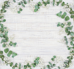 Natural floral frame with eucalyptus branches and white flowers over wood,  flat lay