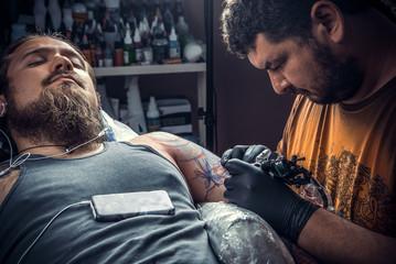 Professional tattoo artist works in tattoo studio