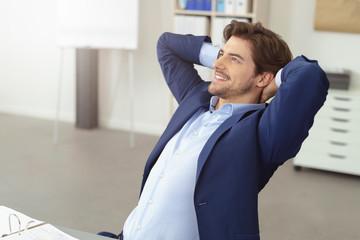 zufriedener mitarbeiter im büro verschränkt die arme hinter dem kopf