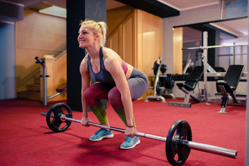 Blonde girl weight lifting at gym