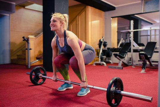 Blonde girl weight lifting at gym