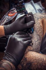 Tattoo master doing tattoo in tattoo parlor
